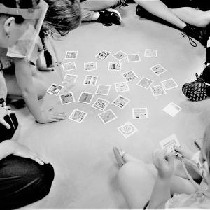 Photos d'un groupe d'enfant assis par terre autour de cartes de médiation que des enfants utilisent pour découvrir l'art de manière ludique