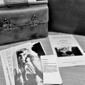 Photo en noir et blanc de sacoches en cuir posées sur une table avec des prospectus d'un spectacle de comédiens de théâtre disposé devant