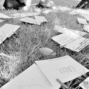 Photo de feuille de papier A4 sur la pelouse entourées d'un groupe de personnes étudiantes, etc