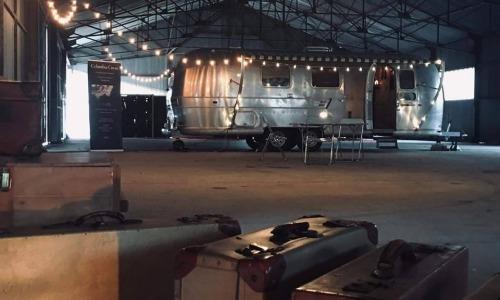 Image d'une caravane dans un hangar avec des guirlandes electriques et des valides en premier plan